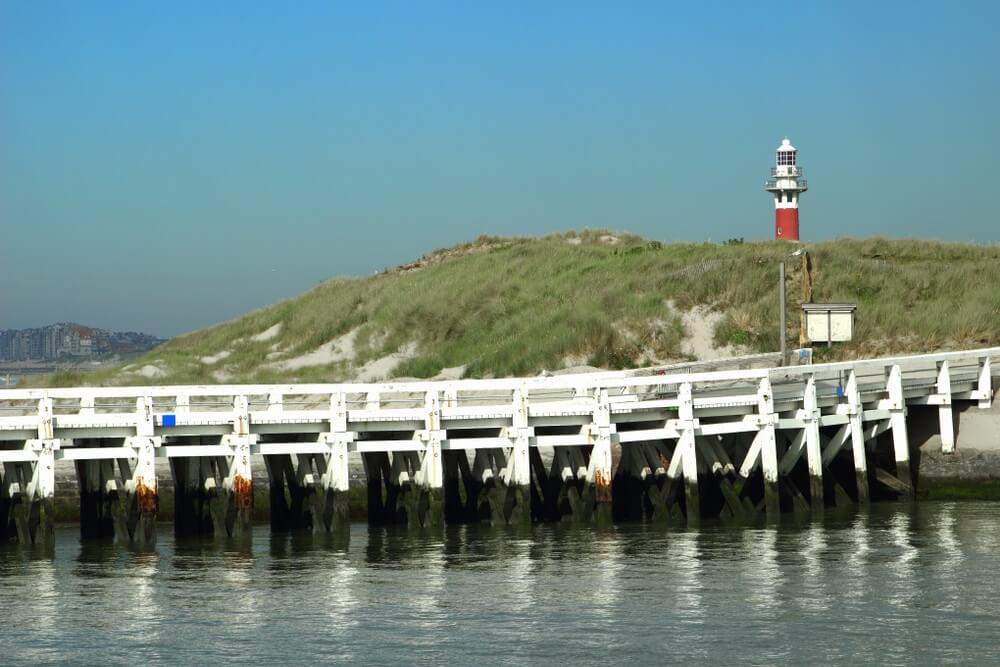 Witte steiger loopt over het water bij het strand bij Nieuwkerk, België. Vuurtoren op de achtergrond.