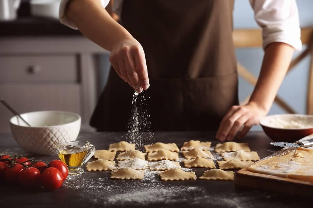 Vrouw maakt verse pasta in de keuken, besprenkeld deze met bloem.