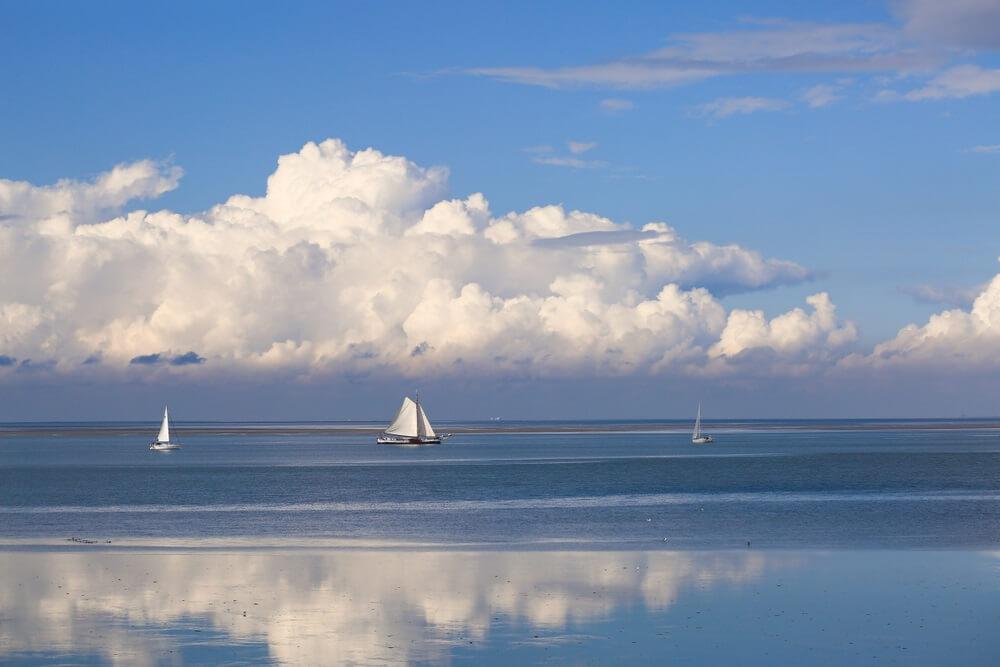 De prachtige Waddenzee in Nederland - Romantisch uitzicht op de blauwe lucht, witte wolken en zeilboten op een zonnige dag. Genomen vanaf de Afsluitdijk.