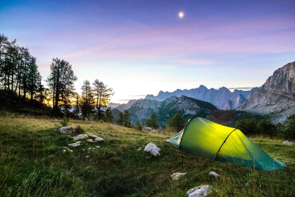 Een tent onder een maan in de nachtelijke hemel in de schemering. Alpen, Triglav Nationaal Park, Slovenië.