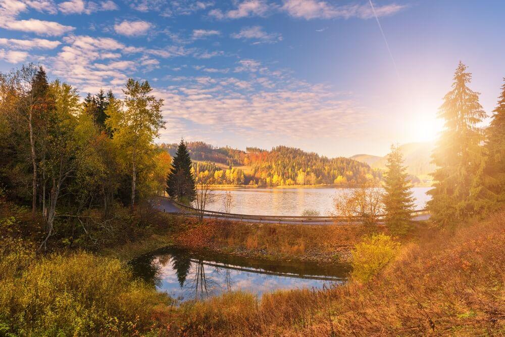 Schilderachtige herfst landschap met gele bomen, blauwe bewolkte hemel en reflectie in het water, Nationaal park Slowaaks paradijs, Slowakije
