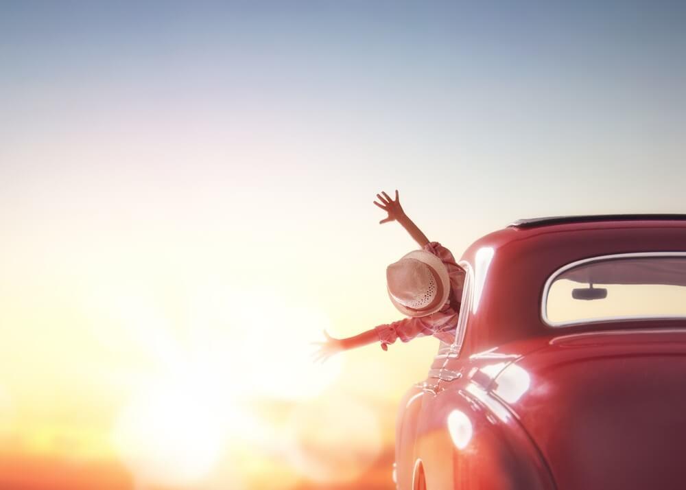 Op weg naar avontuur! Meisje ontspannen en genieten road trip. Gelukkig meisje rijdt in de zonsondergang in vintage auto.