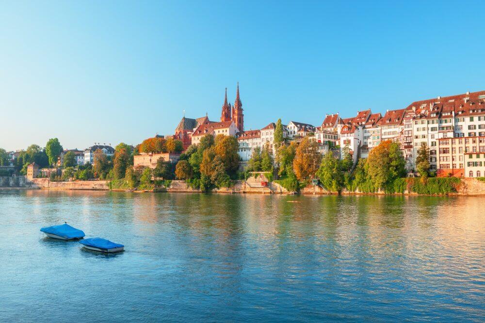 Zonsondergang over de oude binnenstad van Basel en rode steen Munster kathedraal en Rijn, Zwitserland.