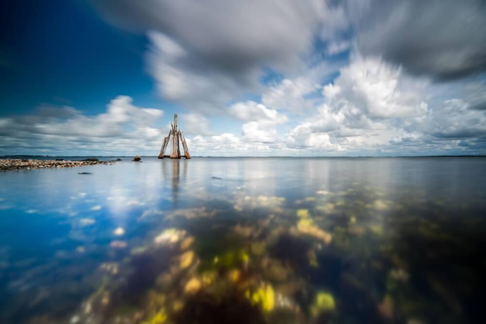 Mooie bewegende bewolkte hemel met witte wolken en blauwe lucht boven een rotsachtig meer met helder water, Arendshoof, Grevelingenmeer, Zeeland.