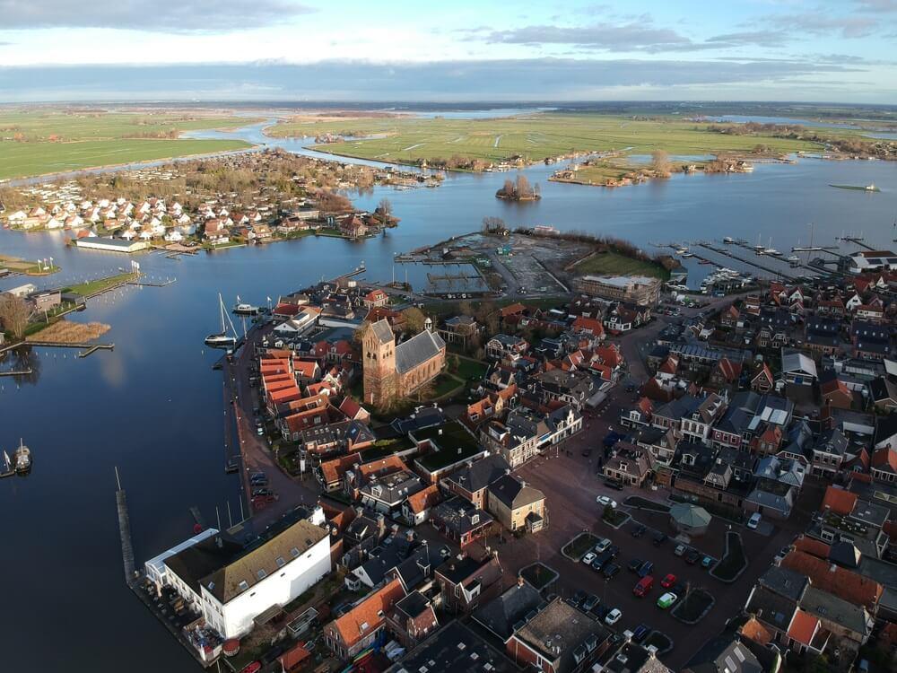 Leuk stadje in de provincie Friesland genaamd Grou. Op een winterdag in december schijnt de zon op de toren van de Sint Piterkerk. Omgeven door water.