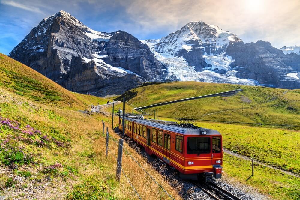 Beroemde elektrische rode toeristische trein die naar beneden komt vanaf station Jungfraujoch (top van Europa) in Kleine Scheidegg, Berner Oberland, Zwitserland, Europa.