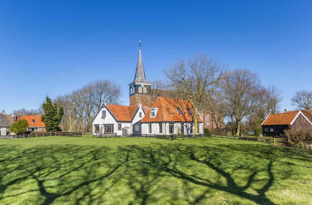 Historische kerk en witte huizen in Makkum, Nederland.