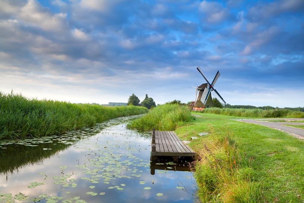 Nederlandse windmolen door rivier met weerspiegelde blauwe hemel, Groningen, Nederland.