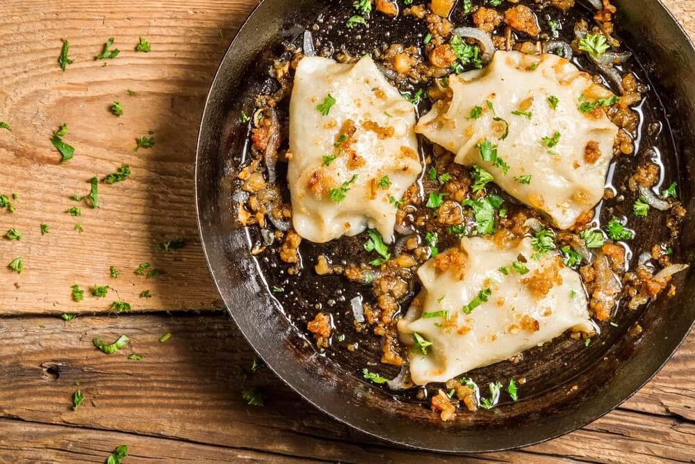 Zelfgemaakte dumplings gebakken met ui en peterselie.