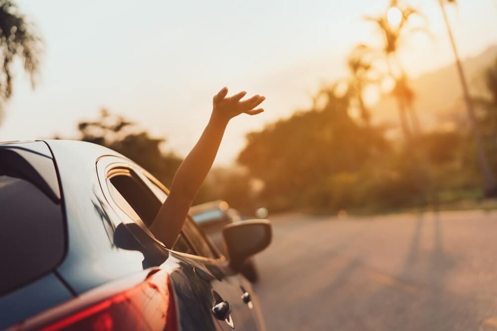 Zomervakantie in blauwe auto bij zonsondergang.