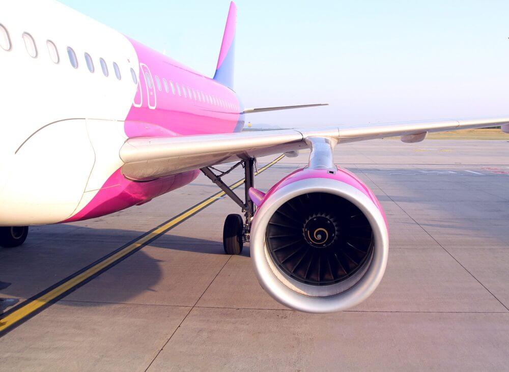 Commerciële vliegtuig detail motor en vleugel geparkeerd op de luchthaven.