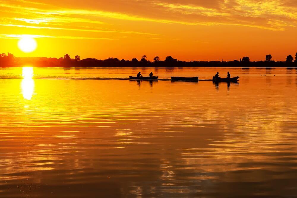 Twee kano's getrokken door een motorboot tijdens prachtige zonsondergang in plas Zoetermeerse.