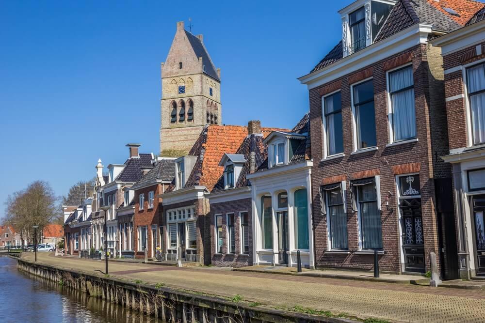 Toren van de martini-kerk langs een kanaal in Bolsward, Nederland.