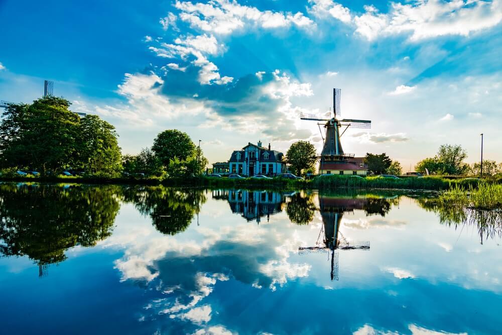 Reflectie van Nederlandse windmolens in de wateren van Kralingse Plas, Rotterdam, Nederland.