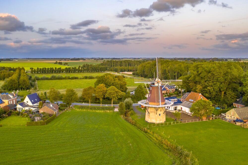 Luchtfoto van zonsondergang over Nederlands dorp in agrarische landschap, Groningen, Nederland.