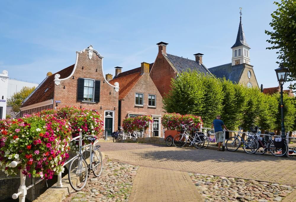 De 'Heerewal' (Herenstraat) met de toren van de Hervormde kerk in het pittoreske vestingstadje 'Sloten', de provincie 'Friesland', Noord-Nederland.