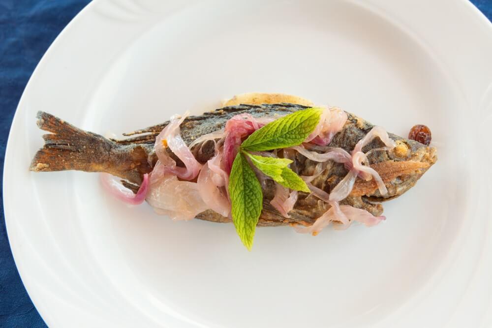 Zeebaars met ui en munt typisch gerecht van de Eolische eilanden in Sicilië.