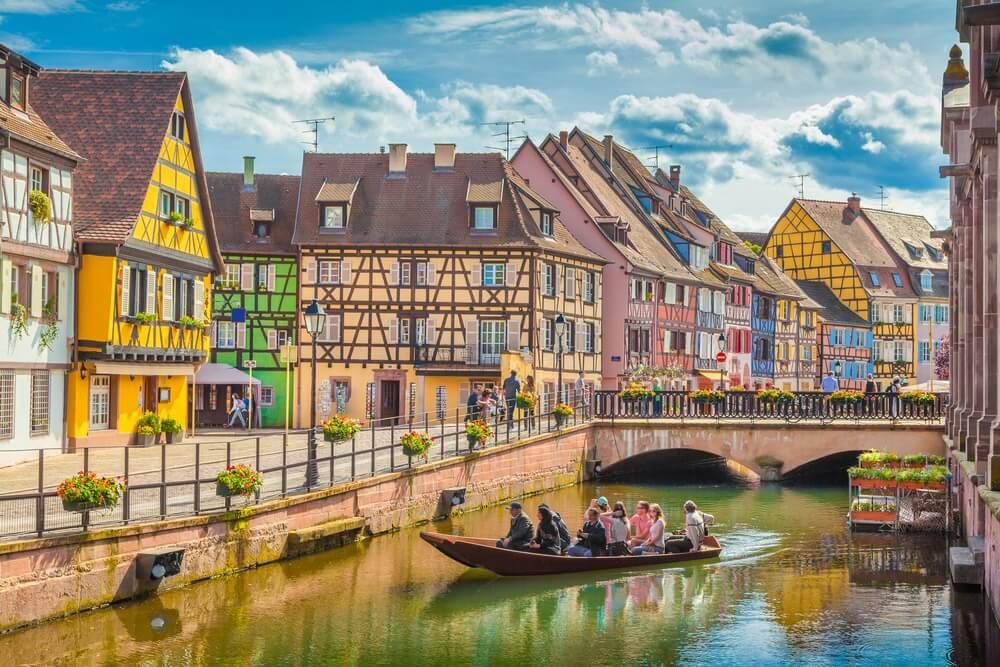 Prachtig uitzicht op de historische stad Colmar, ook bekend als Klein Venetië, met toeristen die een boottocht maken langs traditionele kleurrijke huizen op idyllische rivier Lauch in de zomer, Colmar, Elzas, Frankrijk.
