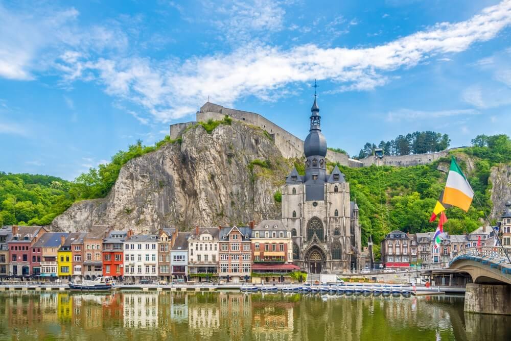 Uitzicht op de dijk van de Maas met huizen en de kerk van Onze-Lieve-Vrouw-Hemelvaart in Dinant, België