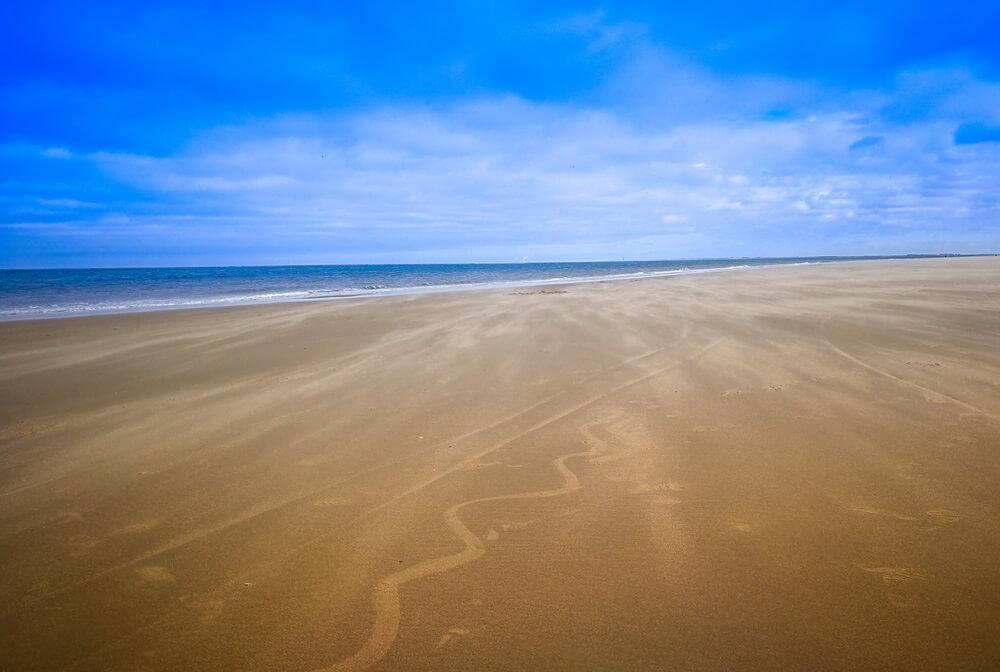 Renesse eenzaam strand met blauwe lucht, Nederland.