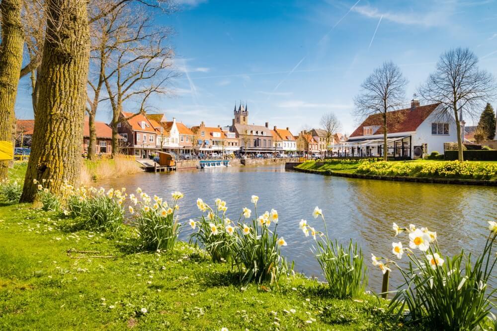Prachtig uitzicht op het historische stadje Sluis op een mooie zonnige dag met blauwe lucht en wolken in het voorjaar, Zeeuws-Vlaanderen, Nederland.