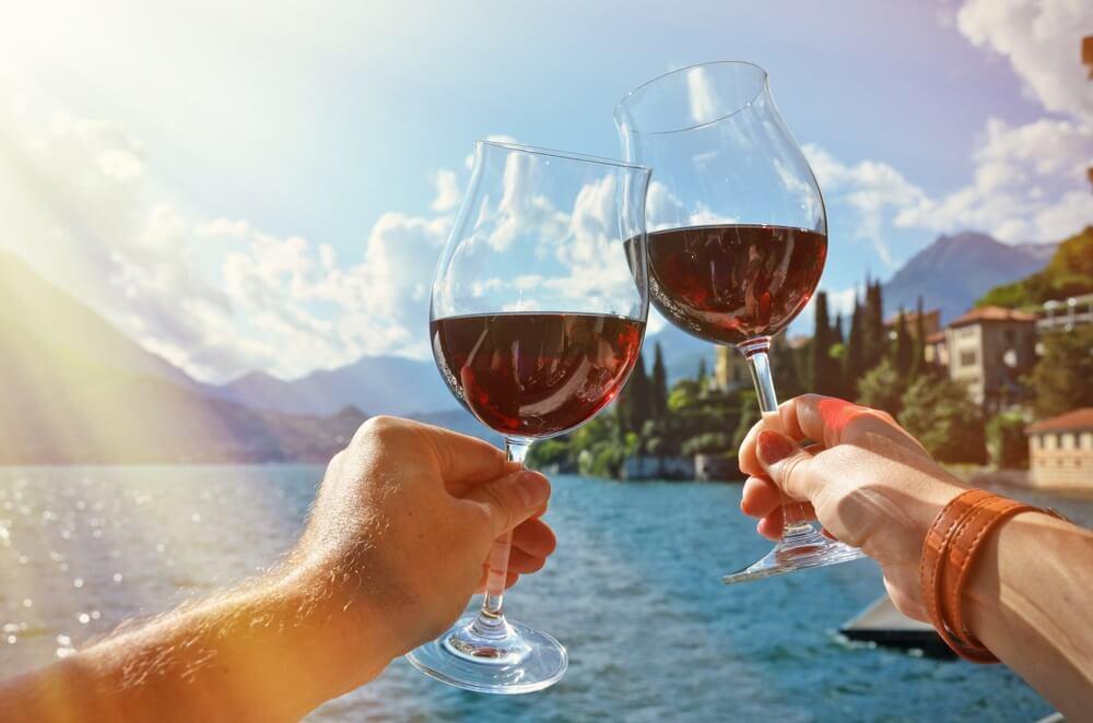 Twee wijnglazen in de handen. Varenna stad aan het Comomeer, Italië.