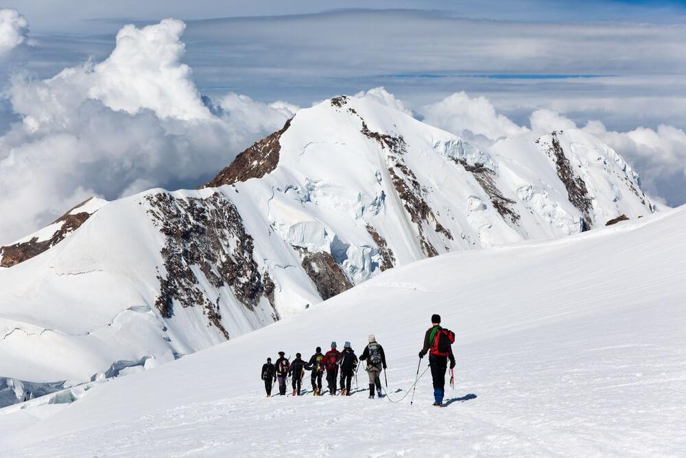 Een grote groep bergbeklimmers die op een gletsjer in een zonnige dag lopen: op de achtergrond de besneeuwde toppen van Lyskamm (4550 mt), Monte Rosa-bereik, Westalpen, Zwitserland, Europa.