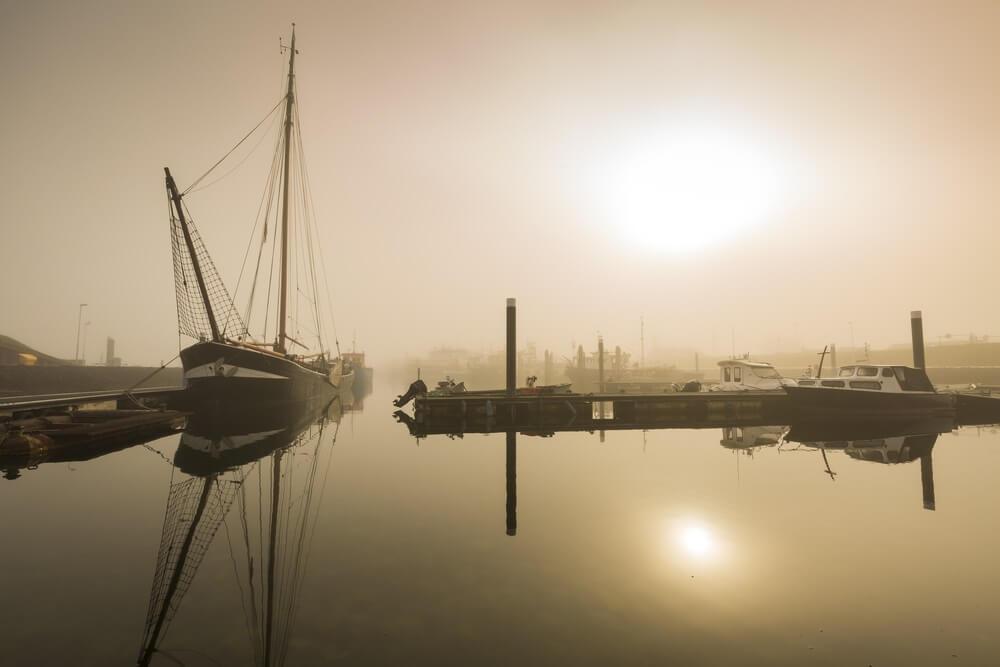 Vissersboten in afwachting van vertraagd vertrek in de haven van Bruinisse, Zeeland, vanwege zware mist tijdens zonsopgang. Kalm water en een vredig landschap met boten in de haven.