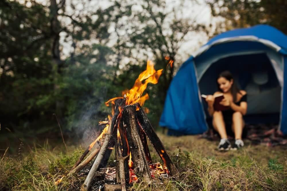 Vrouw reiziger camping op Camping. Jonge vrouw zitten in tent en leesboek in het kamp bij een vreugdevuur..