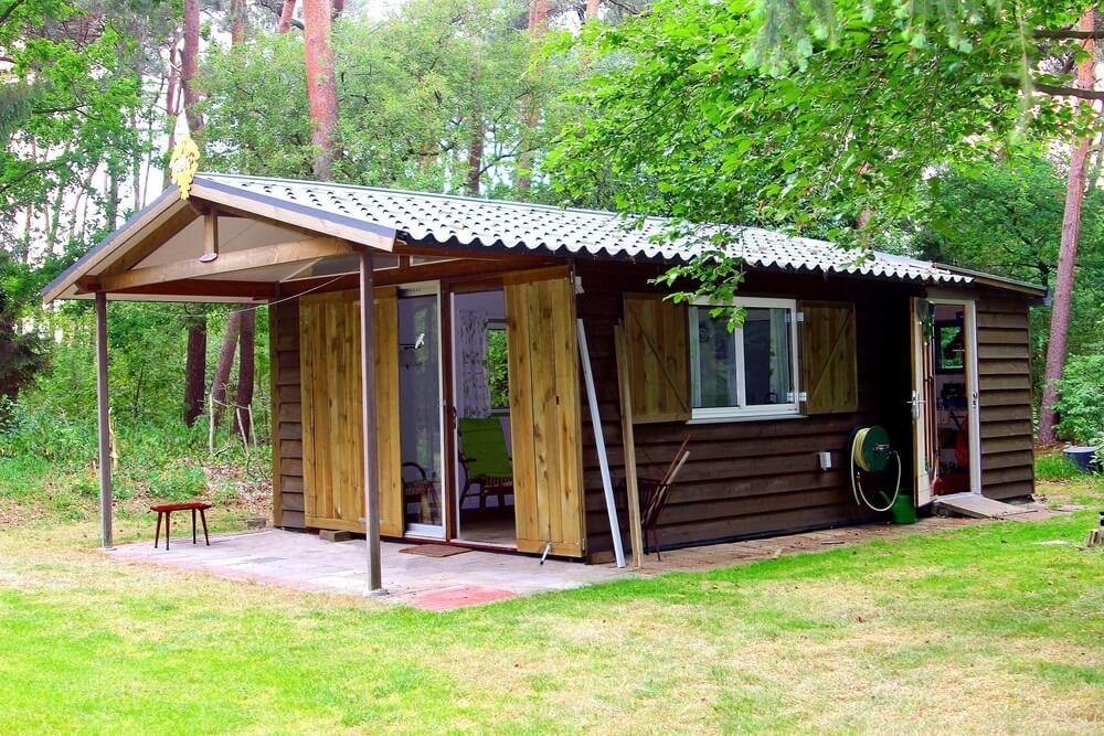Klein huisje met keuken, slaapkamer, badkamer en luiken in groen natuurboslandschap, Drentje.