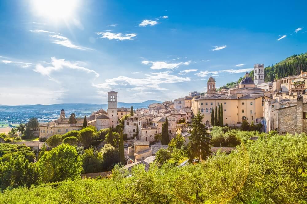 Panoramisch uitzicht op de historische stad Assisi in prachtig gouden ochtendlicht bij zonsopgang op een zonnige dag met blauwe hemel en wolken in de zomer, Umbrië, Italië.