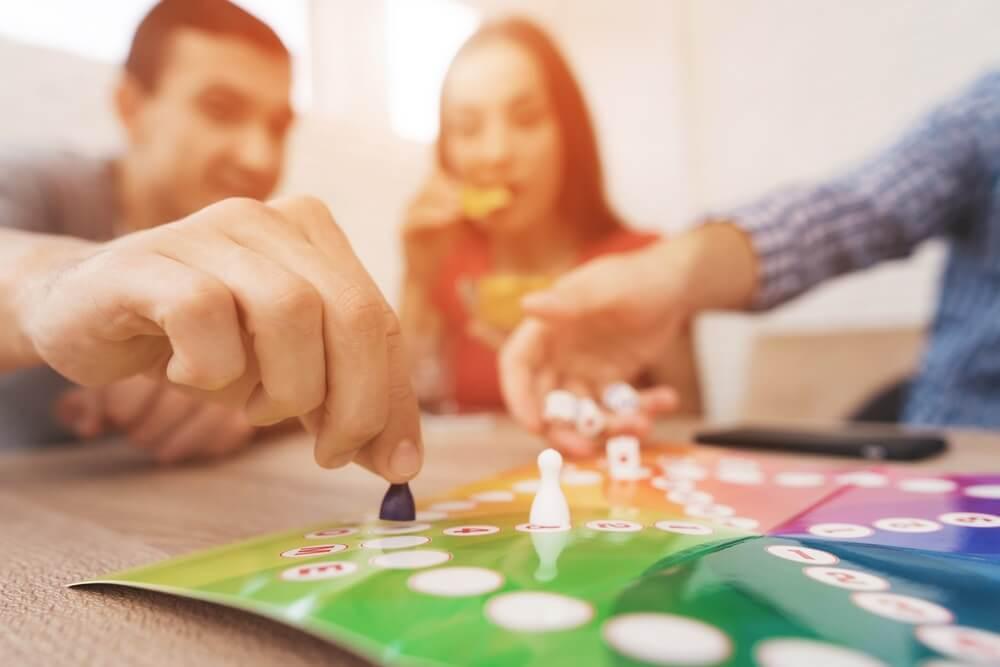 Jongeren spelen een bordspel met behulp van een dobbelsteen en chips. Op tafel hebben ze glazen met alcoholische dranken. Ze hebben plezier met het spelen van een spel.