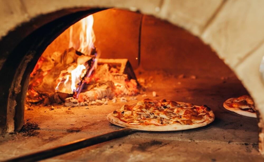 Italiaanse pizza wordt gekookt in een houtgestookte oven.