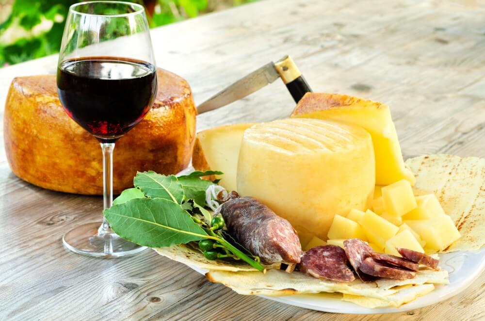 Pecorino-kaas, varkenssalami en rode wijn, typisch Sardijns eten.