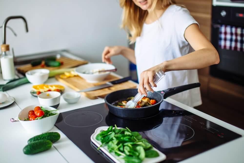 Jonge blonde vrouw koken in de keuken. Gezond eten. Dieet concept. Gezonde levensstijl. Thuis koken. Eten koken.