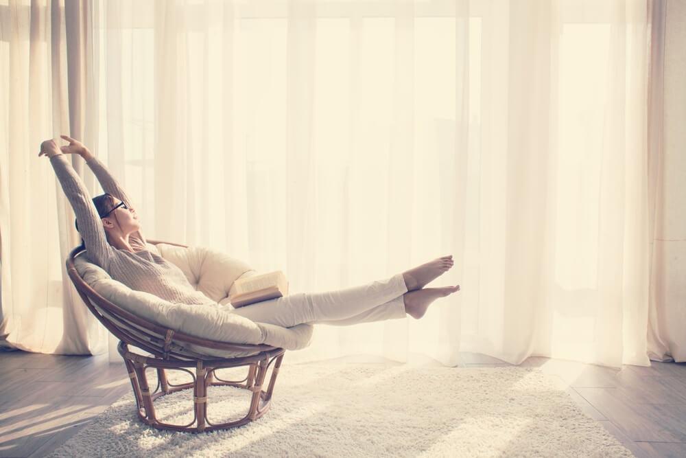 Jonge vrouw thuis zittend op moderne stoel voor het raam ontspannen in haar woonkamer leesboek, instagram toning.