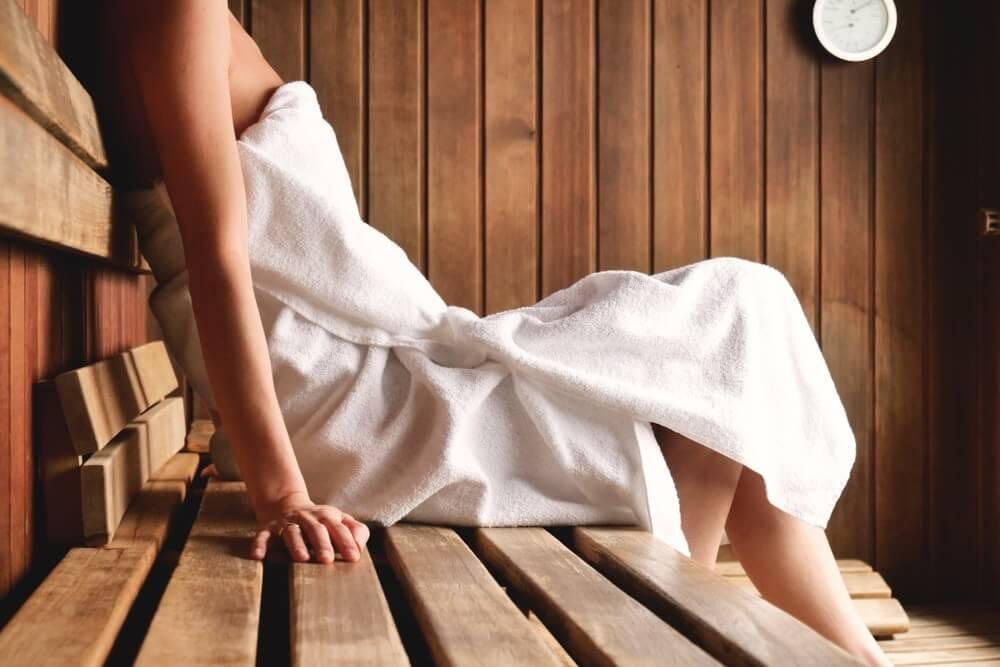 Een mooie vrouw met een witte handdoek neemt een sauna: De sauna is gemaakt van hout met een groot raam met uitzicht op de sneeuw. Concept van: ontspannen, vakantie, wellness centrum.
