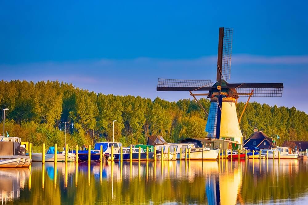 Nederlandse windmolen voor het kanaal met afgemeerde motorboten op jachthaven gelegen in traditioneel dorp in Nederland. Geschoten in Kinderdijk tijdens Golden Hour.