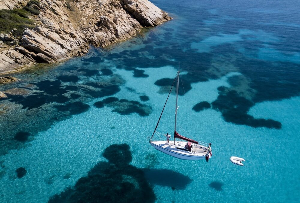 Luchtfoto van een boot voor het eiland Mortorio in Sardinië. Geweldig strand met een turquoise en transparante zee. Smaragdkust, Sardinië, Italië.