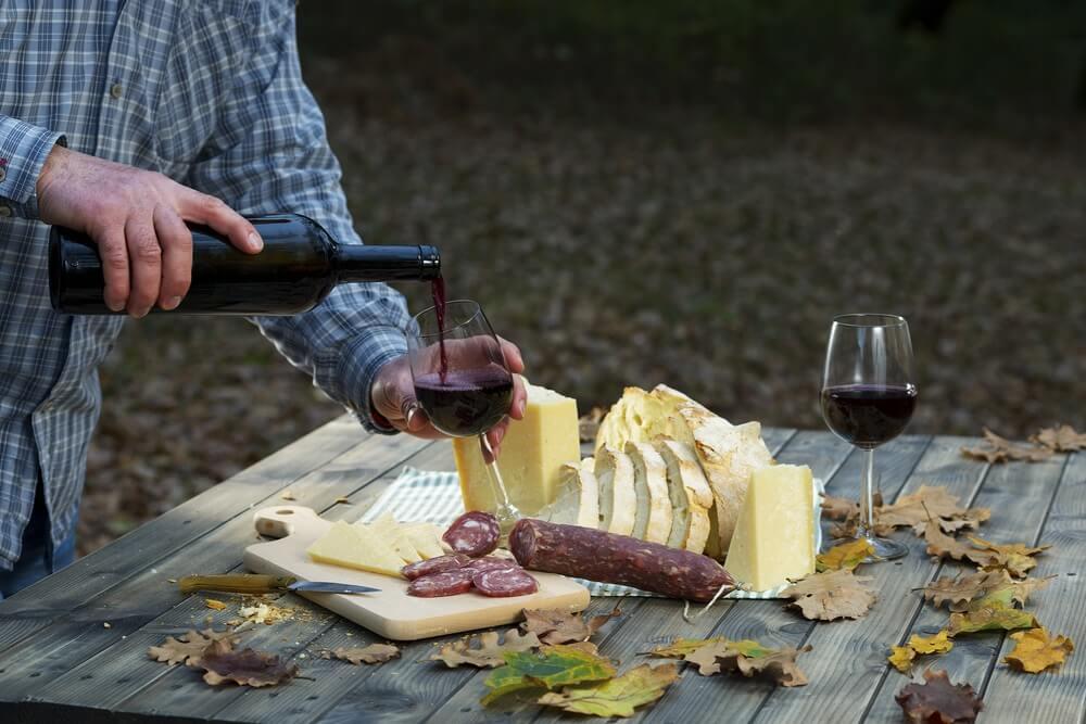 Op de tafel in het hout schenkt drank de wijn in het glas. / Traditioneel diner van Sardinië.