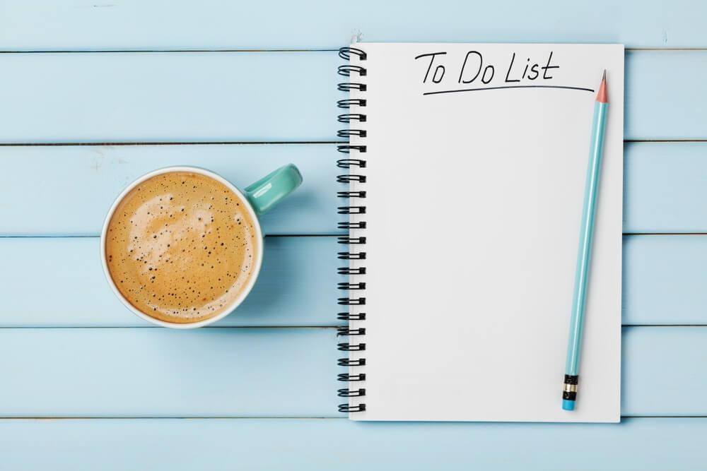 Koffie kop en notitieboek met te doen lijst op blauw rustiek bureau van bovenaf, planning en design concept.