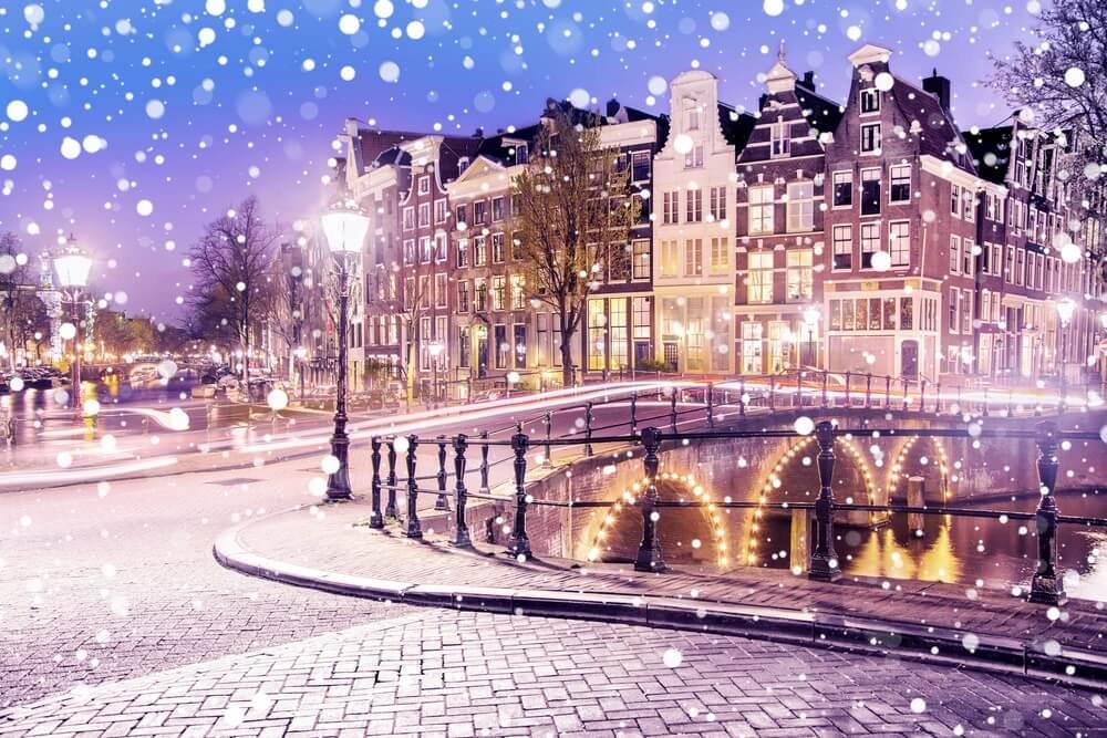 Traditionele Hollandse oude huizen en bruggen op de grachten in Amsterdam op een besneeuwde winteravond, Nederland.