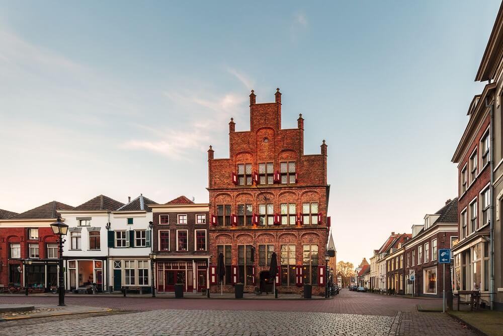 Oude rij huizen met restaurants in de historische Nederlandse stad Doesburg tijdens zonsondergang.