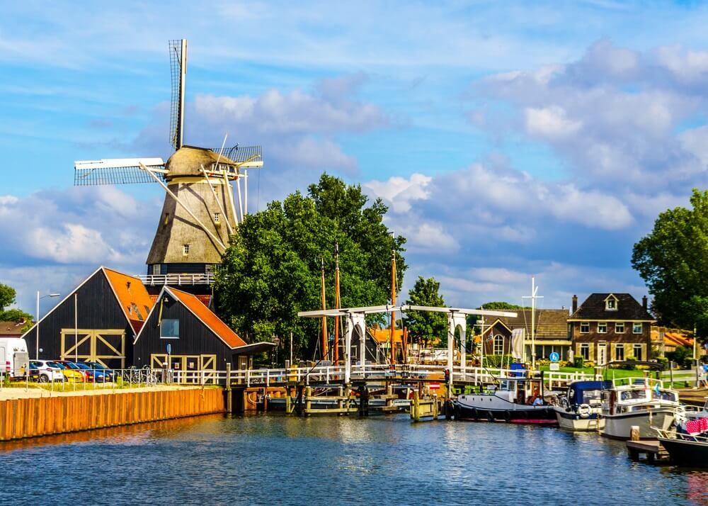 Boten en een ophaalbrug in de haven van Harderwijk in Nederland met een klassieke Nederlandse windmolen.