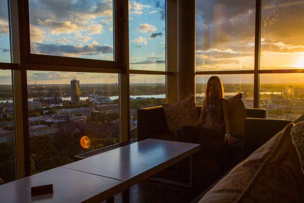 Meisje zit in een skybar bij het raam en bewondert de zonsondergang in Riga, Letland.
