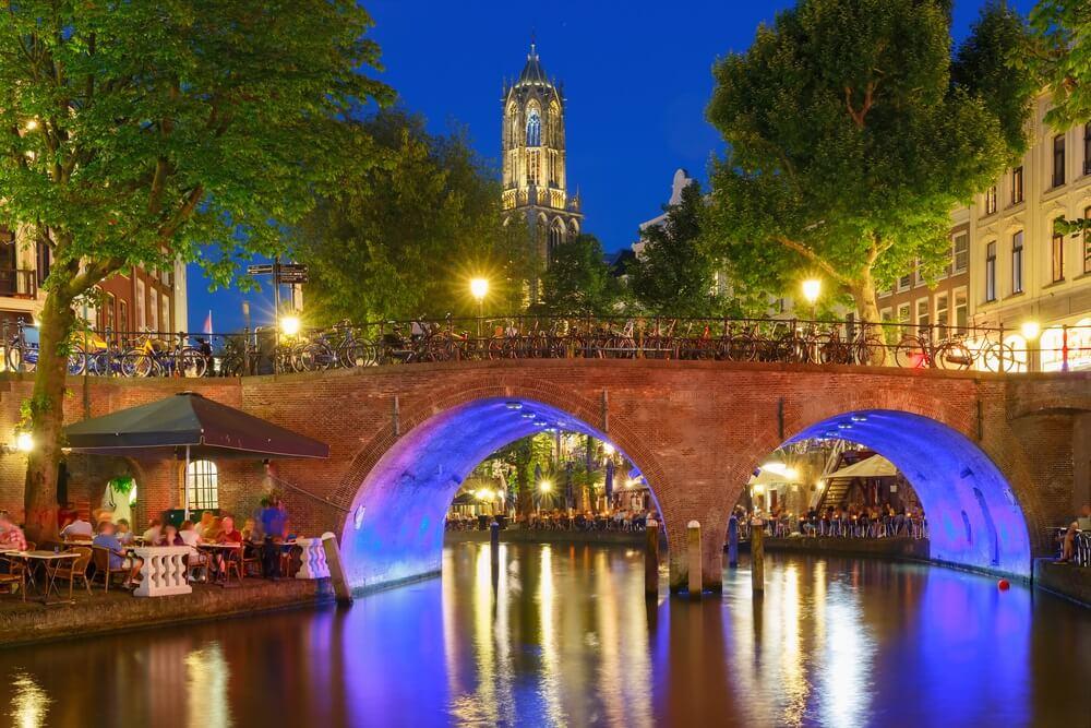 Domtoren en kanaal in de nacht kleurrijke verlichtingen in het blauwe uur, Utrecht, Nederland.