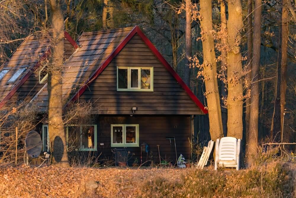 Houten recreatiewoning in bos verlicht door weinig zonlicht.