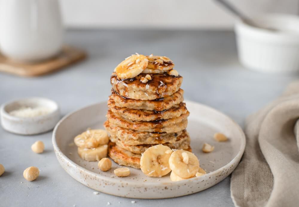 lekkere havermout pannenkoek met banaan, noten en dadelsiroop. grijze achtergrond, horizontaal beeld. Comfortfood.