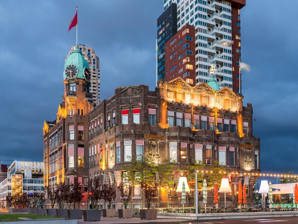 Het prachtige Hotel New York in Rotterdam, in de avond. Hotel met restaurant.