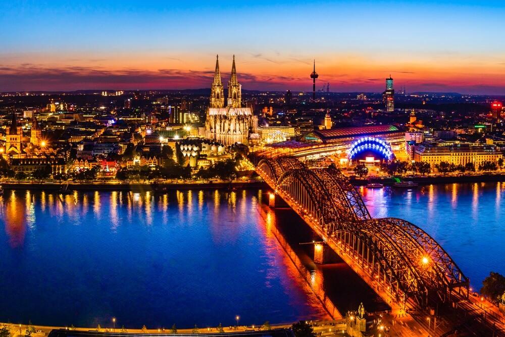 Keulen, Duitsland: Prachtig panoramisch nachtlandschap van de gotische katholieke kathedraal van Keulen, de Hohenzollern-brug en de rivier de Rijn bij zonsondergang, gouden uur en blauwe uur.